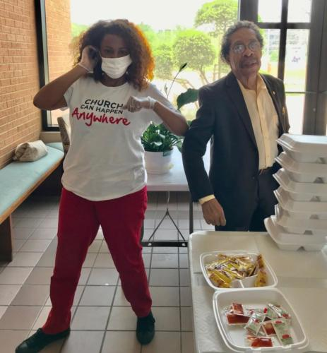 Community leader Thomas Jefferson (at right) stops by Hamilton Park UMC to thank the church for its feeding program. A volunteer next to him shows how the program is following CDC guidelines wearing masks and gloves.